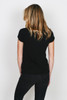 back shows black worn-in tee featuring knotted detailing on the cuffs. This easy tee has unfinished trim throughout. Shown worn with  black pants.