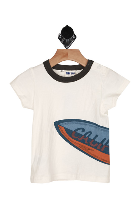 front show white tee with black neckline, snap closure at left shoulder, and half of surfboard design at bottom left printed.