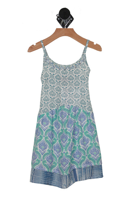 Front shows multi colored blue white and teal patterned summer dress with adjustable spaghetti straps, beading at front collar, and tiered bottom.
