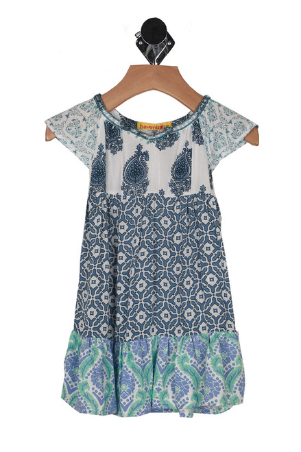 front shows summer dress with contrasting prints in different shades of blues and teals. Beading at top collar.