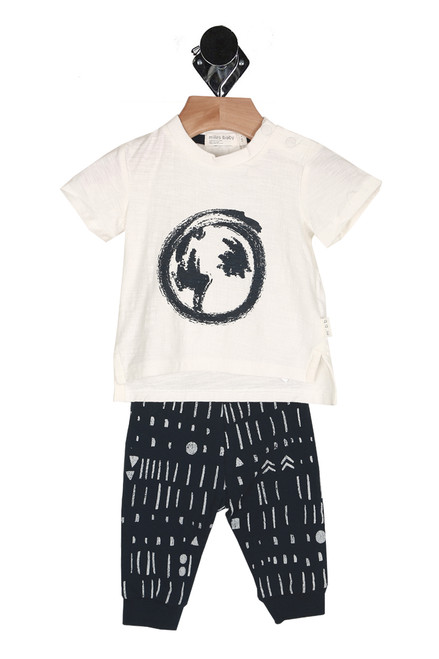 Front shows Two piece white tee top with black outline earth symbol and multi patterned long pants.