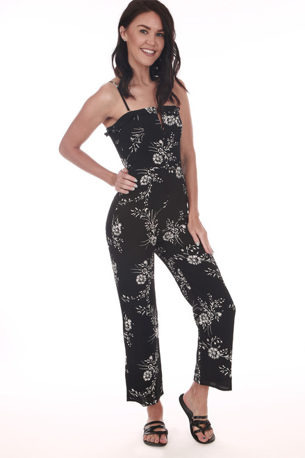 Front shows black ankle length jumper suit with white floral print pattern, spaghetti straps. and small v-shape top. Shown wearing black with sandals.