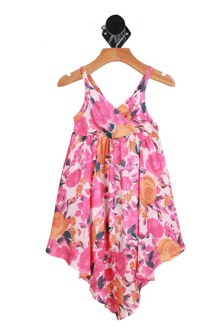 Front shows pink spaghetti strap floral summer dress with v neck and v shape bottom of dress.