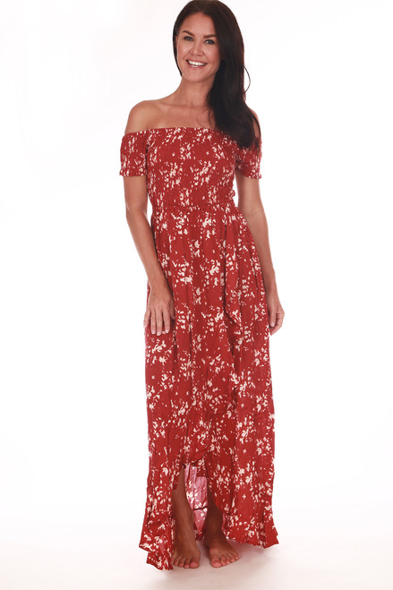 front shows abstract maroon and white splash pattern long dress with off shoulder sleeves, smock top and front slit.