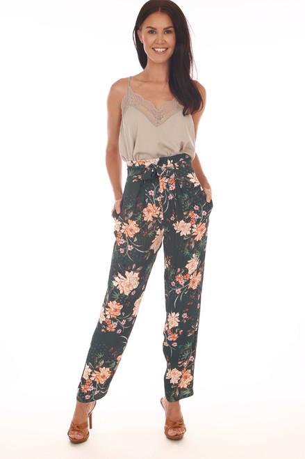 Front shows pink abstract floral print pants with super high rise with belted top, front zipper closure and tapered bottom leg. Shown worn with orange heels and light beige lace spaghetti strap top.