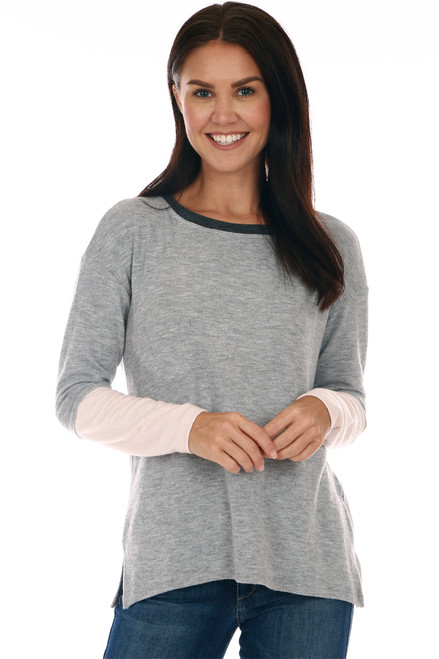 front shows soft grey long sleeve pullover sweat shirt featuring white color blocking at arms with boat dark neckline.