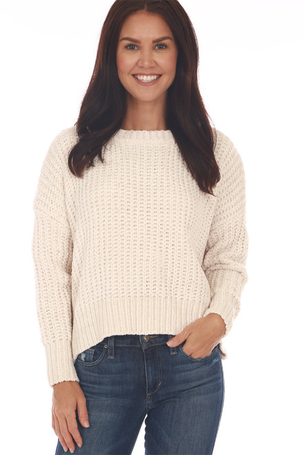 front shows beige colored long sleeve sweater featuring a super soft chenille material with scoop neckline and slightly cropped bottom hemline.Shown worn with blue jeans.