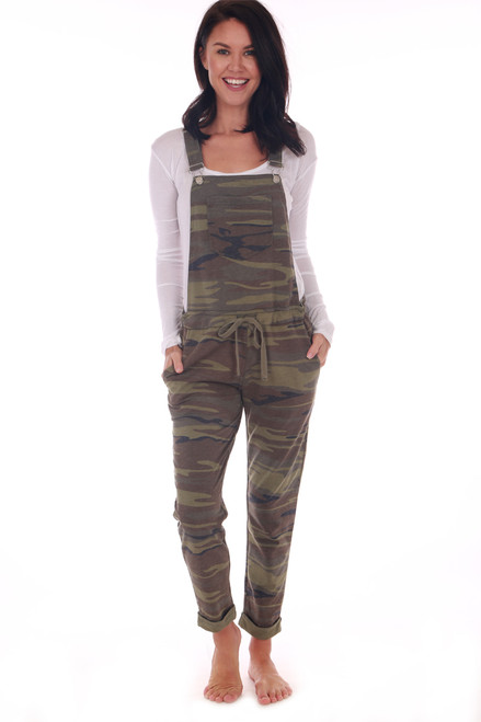 Front shows camouflage overalls featuring the softest jersey material with adjustable overall straps, waist tie and tapered cuffed ankles for the cutest look. Shown worn with a long white sleeve shirt
