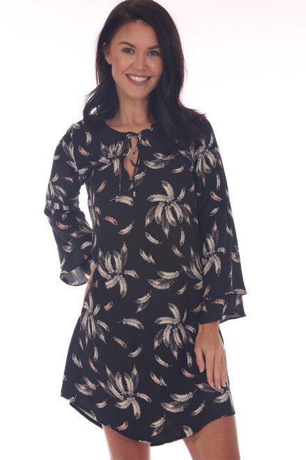 Front shows black long sleeve mini dress featuring an all over feather print with long bell sleeves and front top neck tie and sheer material.