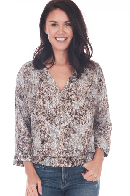 Front shows brown and grey patterned blouse featuring a surplice front with 3/4 length sleeves, dolman fit and elastic band at bottom. Worn with blue jeans.