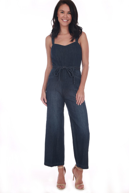 front shows blue denim jumpsuit featuring culotte length pants with thin adjustable tying straps, sash at waist and hidden side zipper.