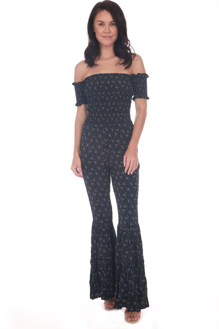 Black floral jumpsuit has a smocked off the shoulder top with smocked short sleeves, flared bottoms and a fitted look.  All over floral print.