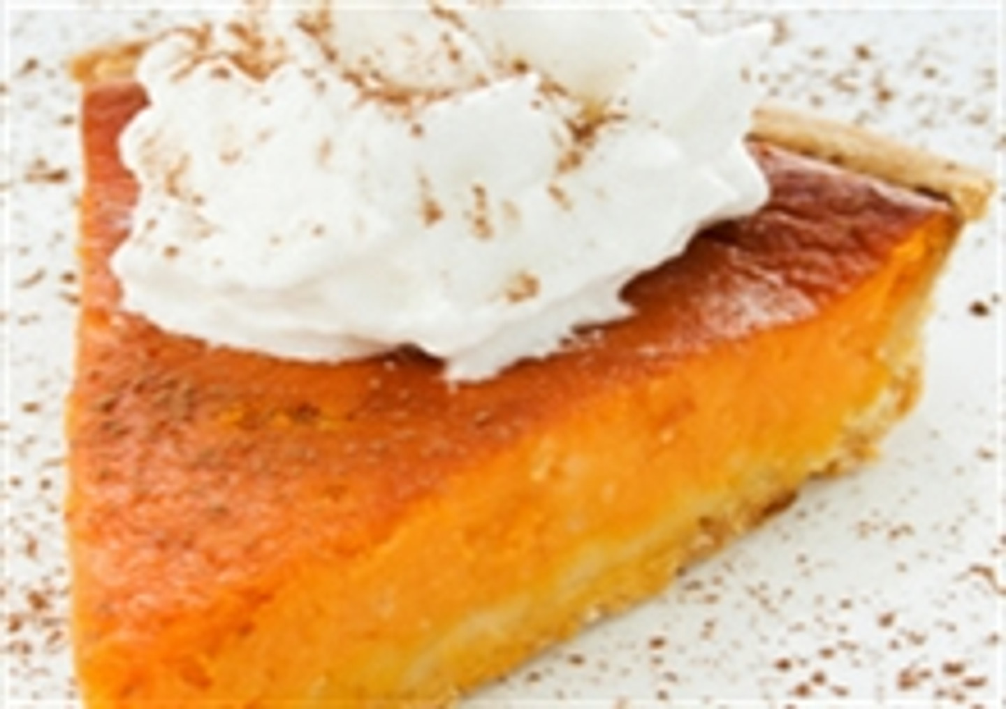 Delicious slice of pumpkin pie with whipped cream and a sprinkle of cinnamon