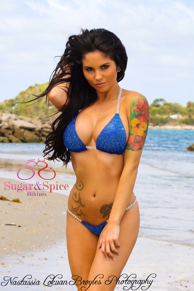 Sugar & Spice Royal Blue Shimmer bikini top with Crystal & Crystal AB Rhinestones in Silver Settings, double jewel straps and jewel connector. • Top is lined. • Optional Padding can be added to top. • Perfect for competition posing bikini! Top and bottom sold separately.  Shown with optional Royal Blue Shimmer bikini bottom with Crystal AB Rhinestones • Your choice of Micro or Brazilian scrunch butt. • Bottom is lined in the front. Custom made in the U.S.A.  Rhinestones: COVERED in over 2,000 Sapphire AB Rhinestones