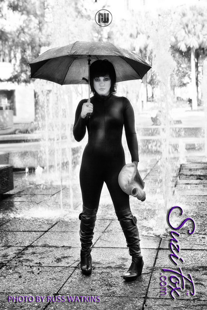 """Customer Picture! Custom Catsuit by Suzi Fox shown in Black Wet Look Lycra Spandex.  Photo by Russ Watkins. You can order this Catsuit in almost any fabric on this site.  • Available in black, red, white, turquoise, navy blue, hot pink, lime green, green, yellow, royal blue, steel gray, neon orange. This is a 4-way stretch fabric with a medium shine. • Your choice of front or back zipper (front zipper shown). • Optional 1 or 2-slider crotch zipper, and """"Selene"""" from Underworld TS Brass zipper, or aluminum circular slider zipper like Catwoman comic characters. • Optional wrist zippers • Optional ankle zippers • Optional finger loops • Optional rear patch pockets • Made in the U.S.A."""