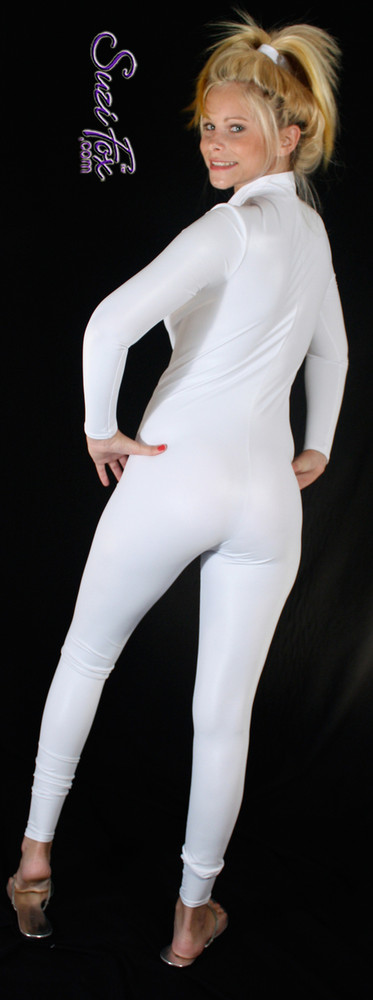 "Custom Catsuit by Suzi Fox shown in White Wet Look Lycra Spandex.  You can order this Catsuit in almost any fabric on this site.  • Available in black, red, white, turquoise, navy blue, hot pink, lime green, green, yellow, royal blue, steel gray, neon orange. This is a 4-way stretch fabric with a medium shine. • Your choice of front or back zipper (front zipper shown). • Optional 1 or 2-slider crotch zipper, and ""Selene"" from Underworld TS Brass zipper, or aluminum circular slider zipper like Catwoman comic characters. • Optional wrist zippers • Optional ankle zippers • Optional finger loops • Optional rear patch pockets • Made in the U.S.A."