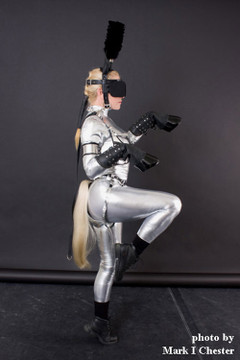 """Customer picture of Custom Catsuit by Suzi Fox shown in Silver metallic foil coated Nylon Spandex.  You can order this Catsuit in almost any fabric on this site.  • Available in gold, silver, copper, royal blue, purple, turquoise, red, green, fuchsia, gun metal, black faux leather/rubber Metallic foil coated spandex. • Your choice of front or back zipper (front zipper shown). • Optional 1 or 2-slider crotch zipper, and """"Selene"""" from Underworld TS Brass zipper, or aluminum circular slider zipper like Catwoman comic characters. • Optional wrist zippers • Optional ankle zippers • Optional finger loops • Optional rear patch pockets • Made in the U.S.A."""