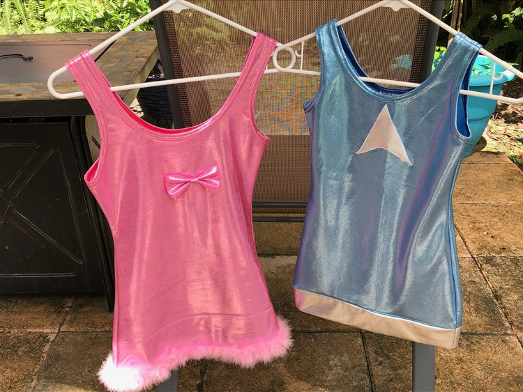 """Child size dress from the movie """"Romy & Michele's High School Reunion"""" by Suzi Fox. PINK DRESS: • fur/feathers at hem • bow at bodice • flared skirt  BLUE DRESS: • silver applique at chest • silver hem trim • flared skirt"""