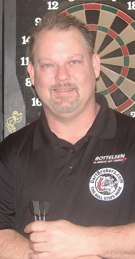 Pro dart player Bryan Stamey with a Dart Brokers patch in front of a soft tip dart board