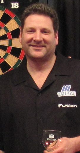 Pro dart player Kevin Jinkensen wearing a TIGA patch in front of a soft tip dart board