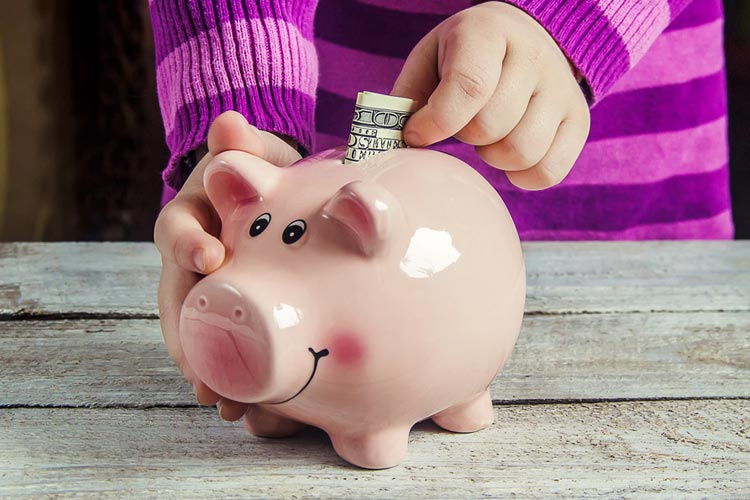 child-putting-money-in-a-piggy-bank.jpg