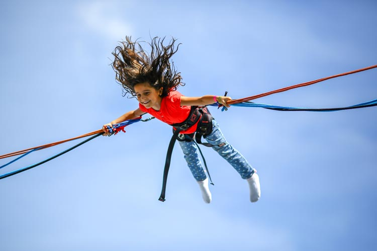 girl-enjoying-a-bungee-jumping-carnival-ride.jpg