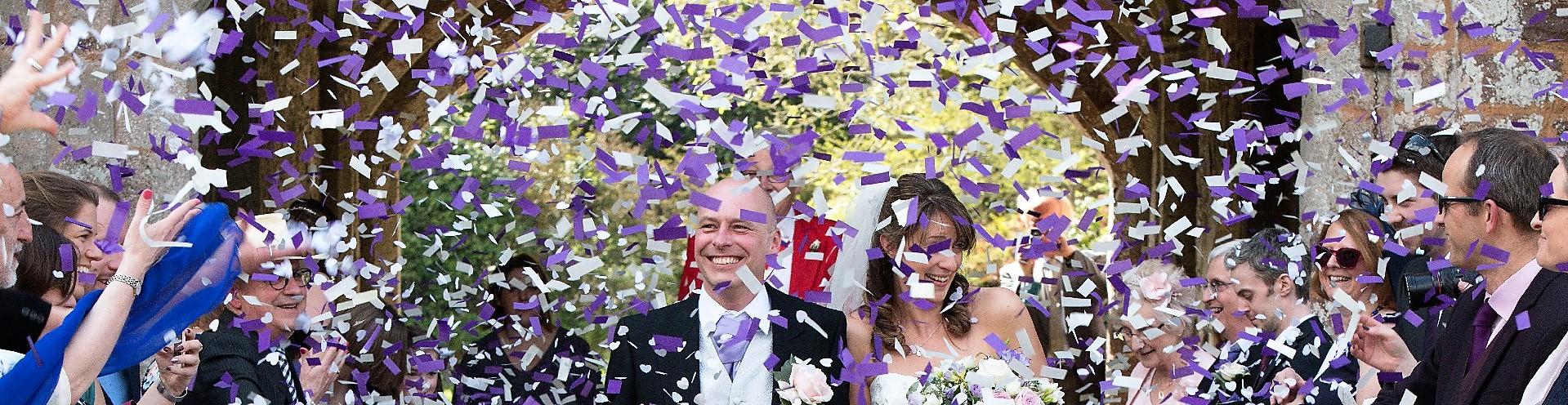 wedding confetti cannons shoot confetti over bride and groom