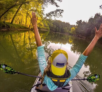 Lady with her arms up while riding a kayak.