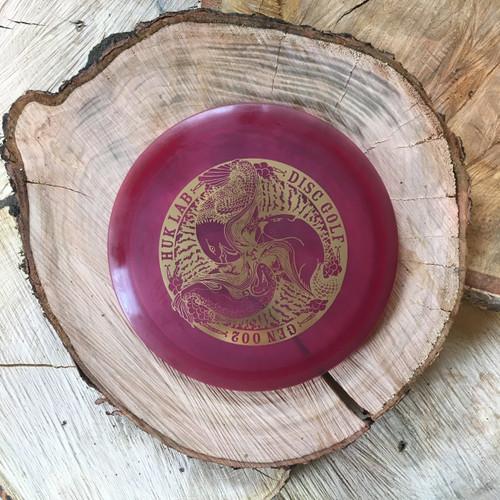 Innova Champion Teebird plum with a gold Huk Lab GEN 004 stamp