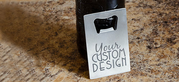 A laser engraved credit card bottle opener leaning up against a bottle on a granite counter top.