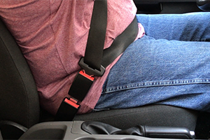 "A black, 3"" rigid seatbelt extension is buckled in to a seat belt on both ends, securing a man wearing jeans and a red shirt in the driver's seat of his car."