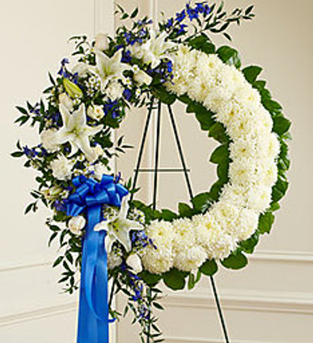 "•Standing wreath arrangement of fresh blue delphinium arranged with white roses, lilies, mums, carnations, monte casino and more •Accented by variegated pittosporum, ruscus and salal •Appropriate for family, friends and business associates to send directly to the funeral home •Our florists use only the freshest flowers available so colors and assortment may vary •Arrangement measures approximately 32""H x 28""W without easel"